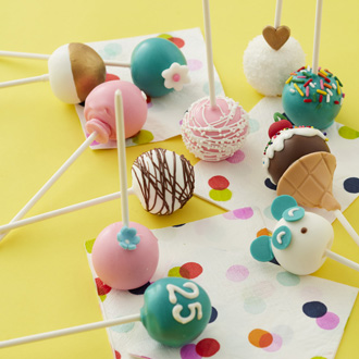 Eleven cake pops arranged on a bright colored surface with designs taught in class.