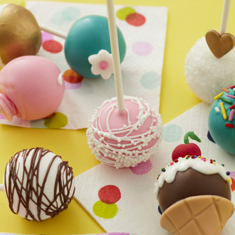 Close-up of colorful drizzled cake pops with sprinkles and fondant appliques.