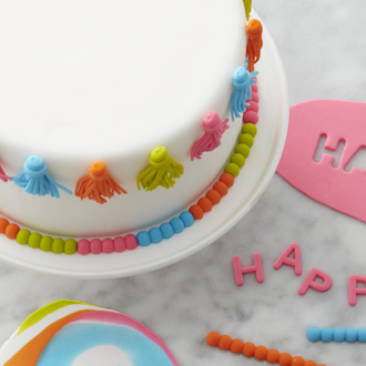 Close-up of fondant covered cake with tassels and a fondant bead border.