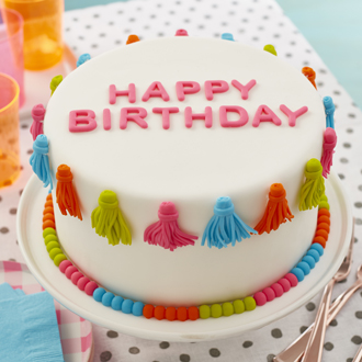 """Finished fondant cake design with tassels, bead boarder, and """"Happy Birthday"""" message."""