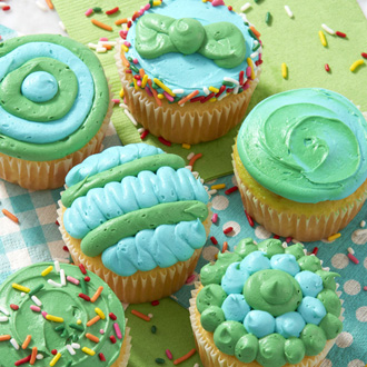 Green and blue buttercream cupcakes decorated with dots, lines, zig zags, and sprinkles.