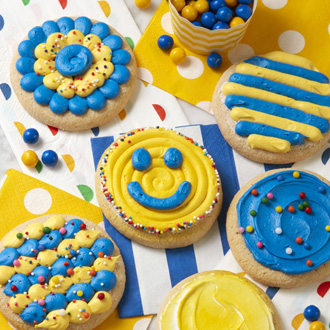Blue and yellow cookies decorated with dots, stripes, smiley faces, and sprinkles.