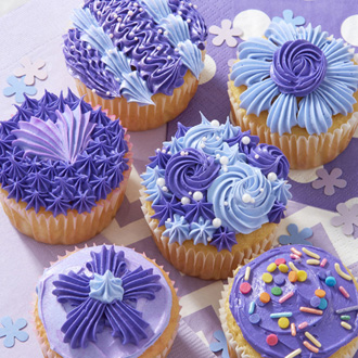 Purple buttercream cupcakes decorated with stars, rosettes, shells, zig zags, and sprinkles.