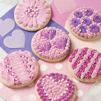 Pink cookies decorated for Valentine's Day with stars, rosettes, shells, and hearts.