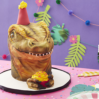 Realistic sculpted fondant dinosaur head cake wearing a birthday hat and holding a cupcake