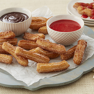 Mini churros on a silver plate with dipping bowls of chocolate and strawberry sauce on the side