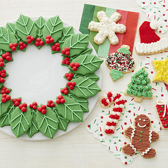 Cookies decorated and arranged like a holly wreath alongside traditional christmas cookie shapes.