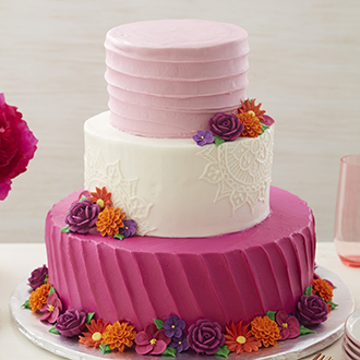 Three-tiered pink and white cake with a bottom border of pink, purple, and orange piped flowers.