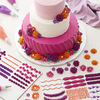 Three-tiered pink and white cake with floral accents, surrounded by piping practice boards.