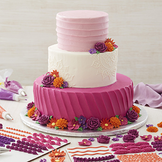 Three tiered cake decorated with floral accents and practice boards covered with piping designs.