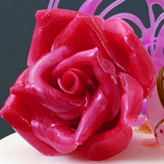 Close-up of pulled Isomalt rose on top of fondant cake.